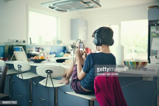Mixed race boy sitting in kitchen listening to cell phone