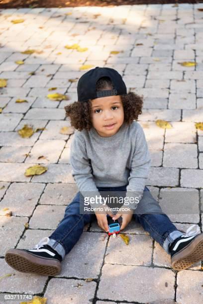 mixed race boy sitting on brick patio - roberto ricciuti foto e immagini stock