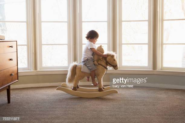 Mixed Race boy sitting on rocking horse near window