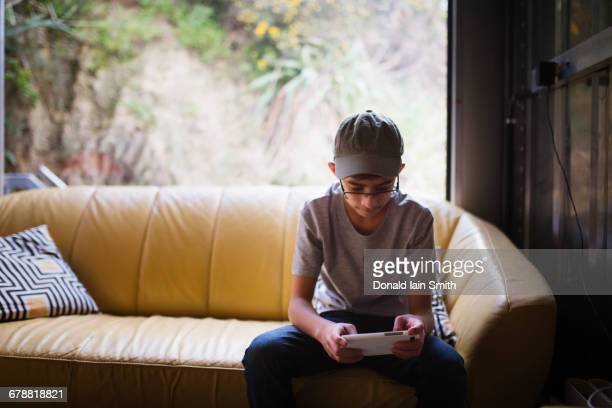 Mixed Race boy sitting on sofa near window texting on cell phone