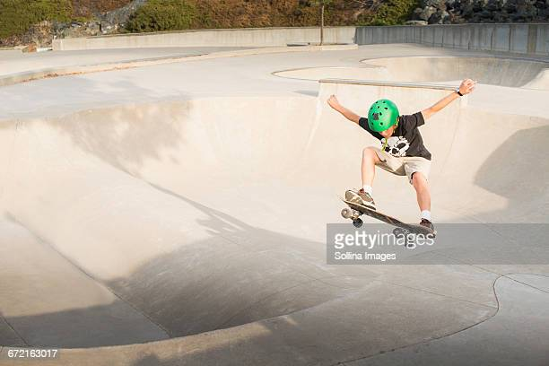 Mixed Race boy skateboarding in skate park