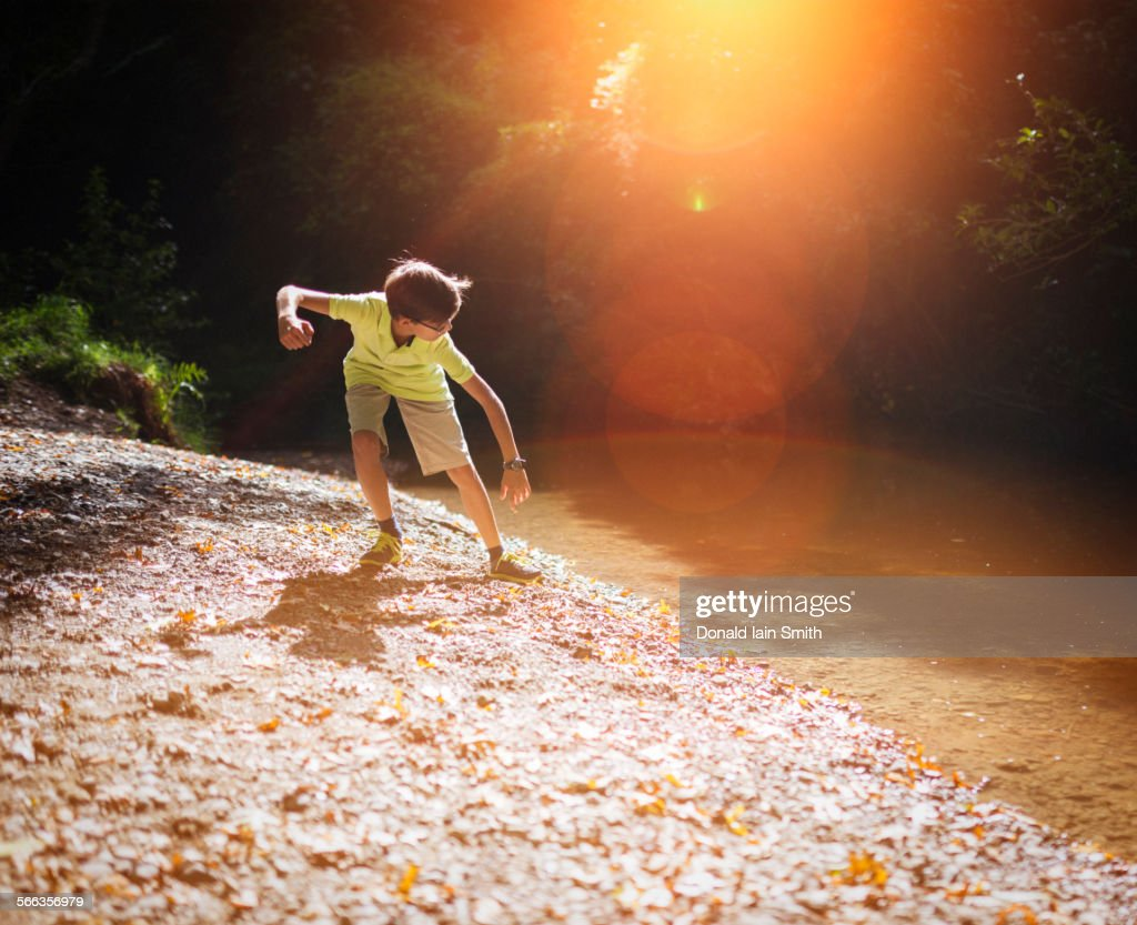 Mixed race boy skipping stones in stream : Stock Photo