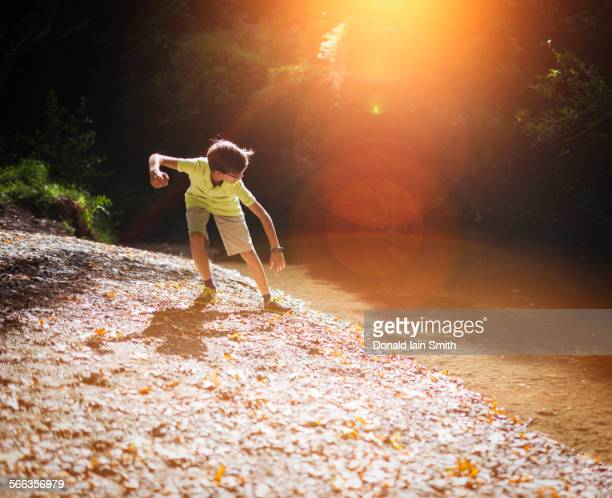 Mixed race boy skipping stones in stream