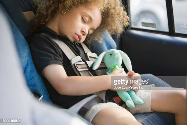 Mixed race boy sleeping in car seat
