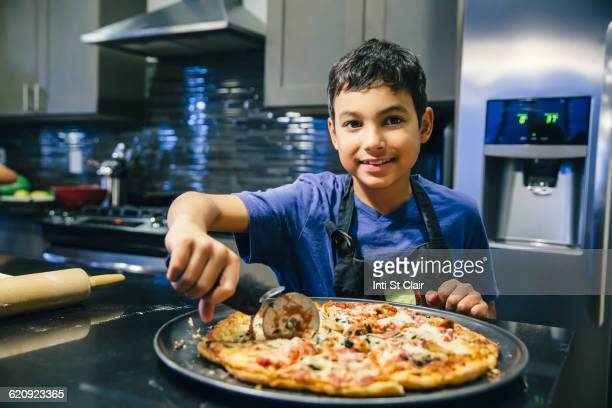 Mixed race boy slicing pizza in kitchen