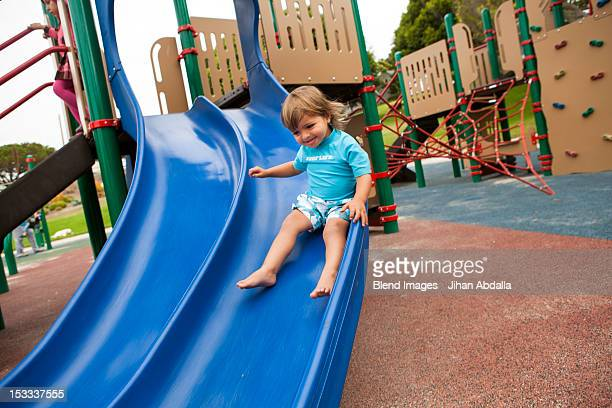 Mixed race boy sliding down slide on playground