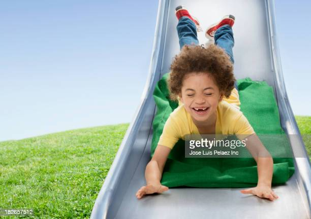 Mixed race boy sliding down slide