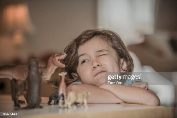 Mixed race boy squinting at toy animals