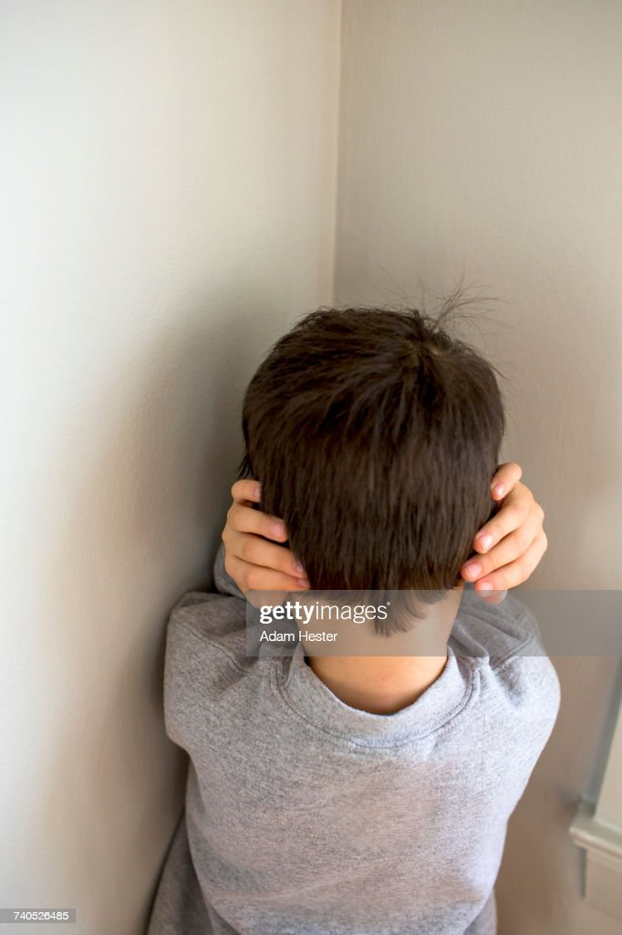 Mixed Race boy standing in corner covering ears : Stock Photo