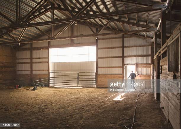 Mixed race boy standing in doorway in barn