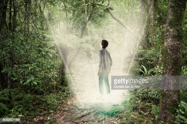 Mixed race boy standing in forest portal