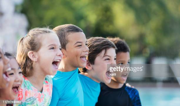 mixed race boy standing with multi-ethnic friends, shouting - children only stock pictures, royalty-free photos & images