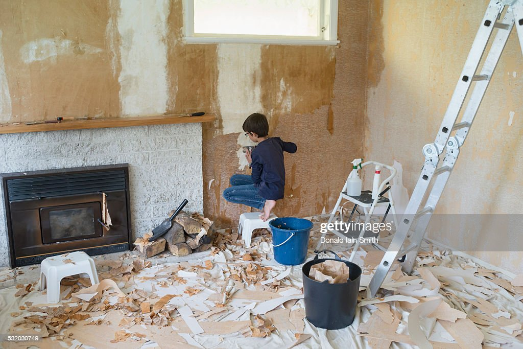 Mixed Race Boy Stripping Wallpaper In Living Room Stock Photo