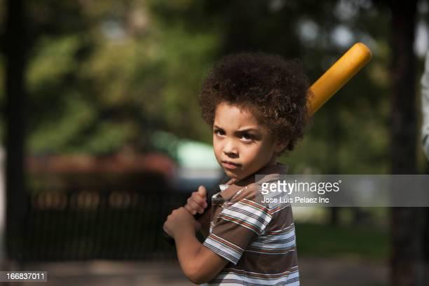 Mixed race boy swinging baseball bat in park
