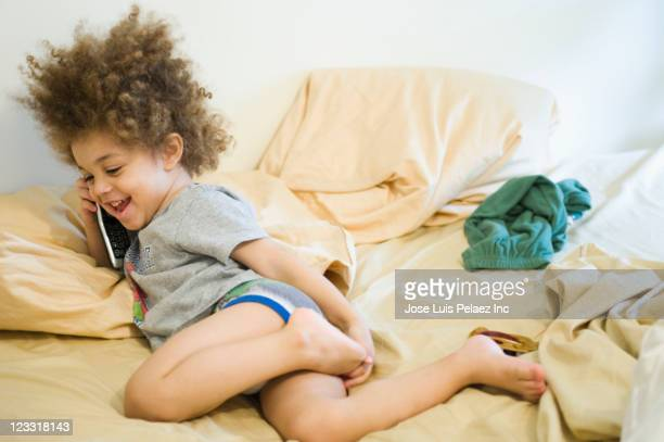 mixed race boy talking on cell phone in bed - bambini in mutande foto e immagini stock