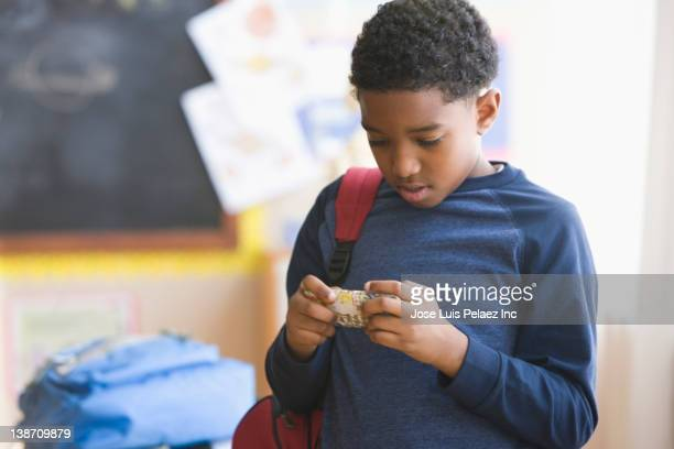 Mixed race boy text messaging on cell phone in classroom