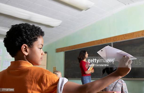 Mixed Race boy throwing paper airplane in class