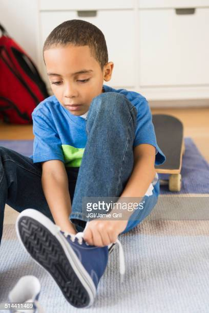Mixed race boy tying his shoelaces