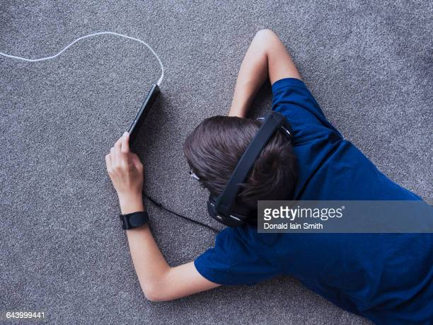 Mixed race boy using cell phone on floor