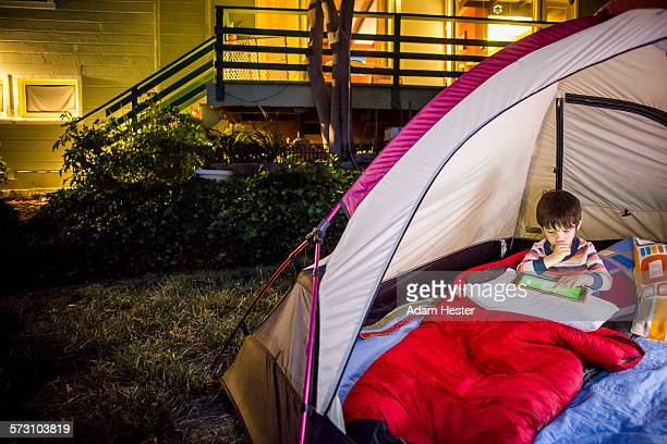 Mixed race boy using digital tablet in backyard tent