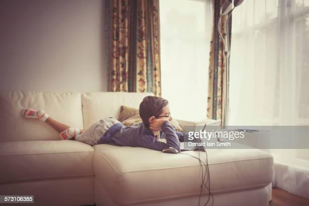 Mixed race boy using digital tablet on sofa