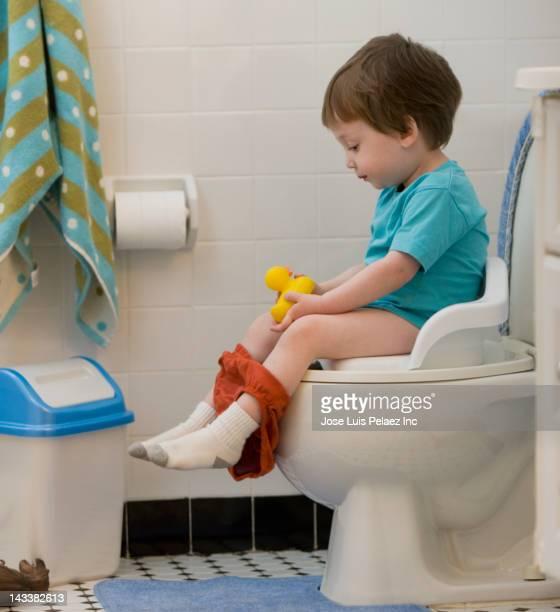 Mixed race boy using toilet