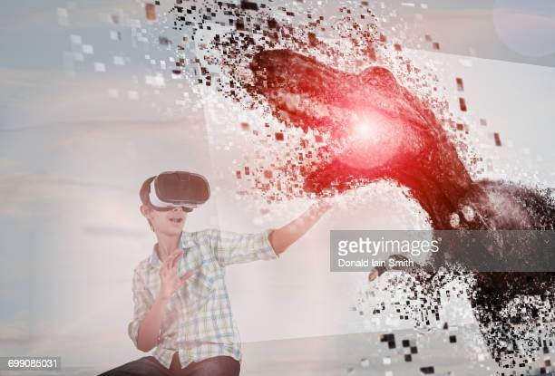 Mixed Race boy using virtual reality goggles watching dinosaur
