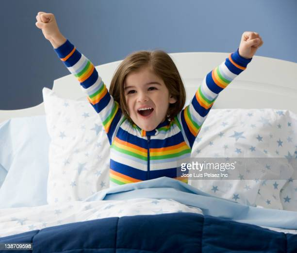 Mixed race boy waking up in bed