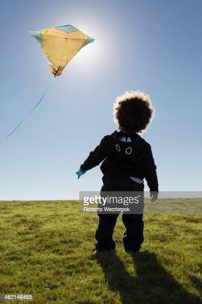 mixed race boy watching kite flying against blue sky - roberto ricciuti foto e immagini stock