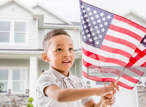 Mixed race boy waving American flag