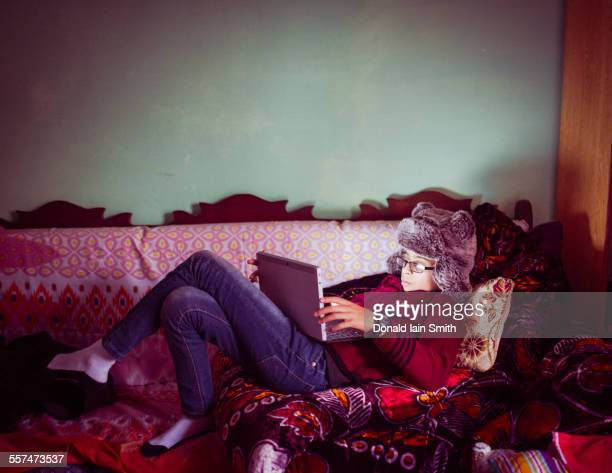 mixed race boy wearing fur hat using digital tablet on sofa - pakistani boys stock photos and pictures