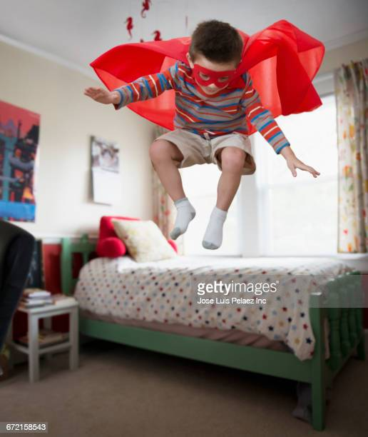 mixed race boy wearing superhero costume jumping off bed - flowing cape stock pictures, royalty-free photos & images