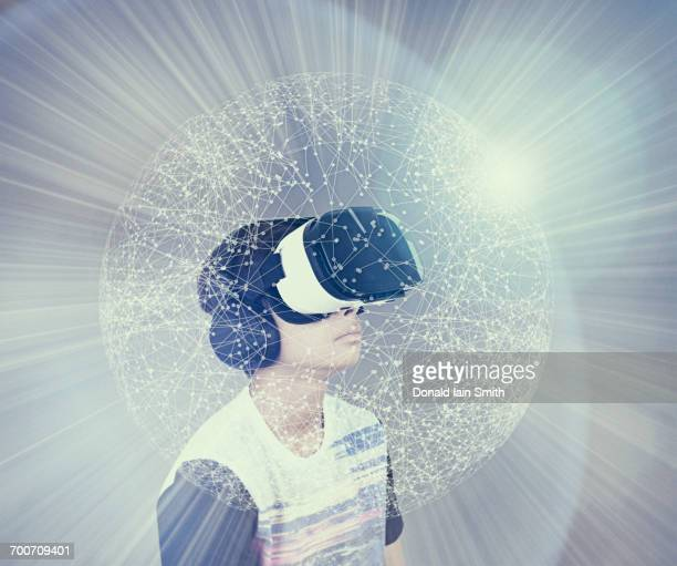 Mixed Race boy wearing virtual reality goggles in glowing sphere
