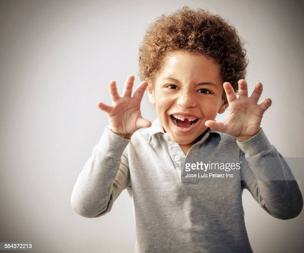Mixed race boy with curly hair and missing tooth growling