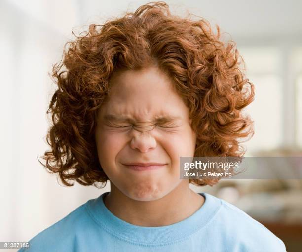 Mixed Race boy with eyes closed tightly