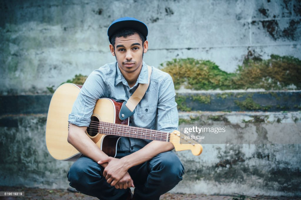 Mixed race boy with guitar crouching on urban sidewalk : Stock Photo