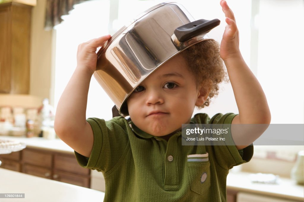 Mixed race boy with pot on his head : Stock Photo