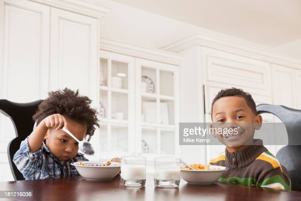 Mixed race boys eating at table