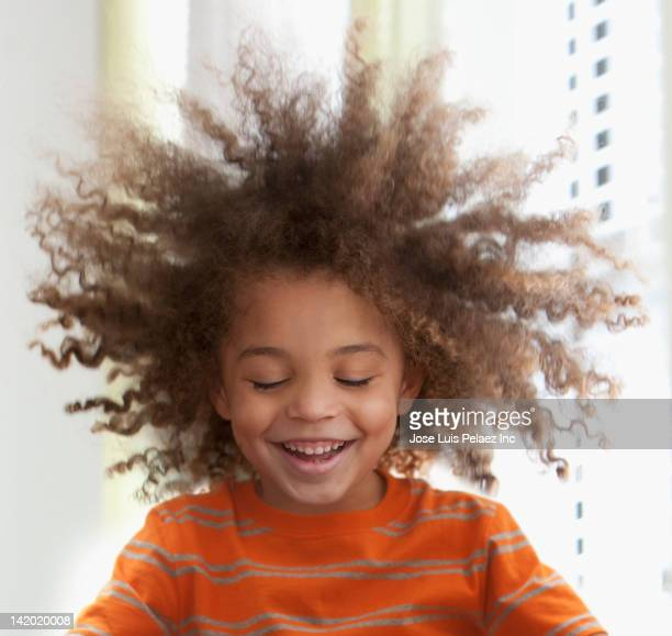 Mixed race boy's hair standing on end