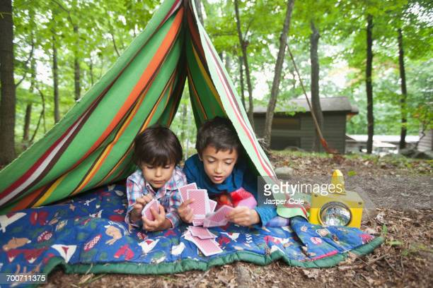 Mixed Race boys playing card game in blanket fort
