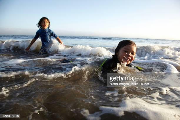 Mixed race boys swimming in ocean
