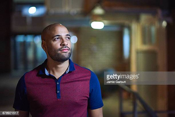 mixed race british male stood outside his flat - introspection stock pictures, royalty-free photos & images