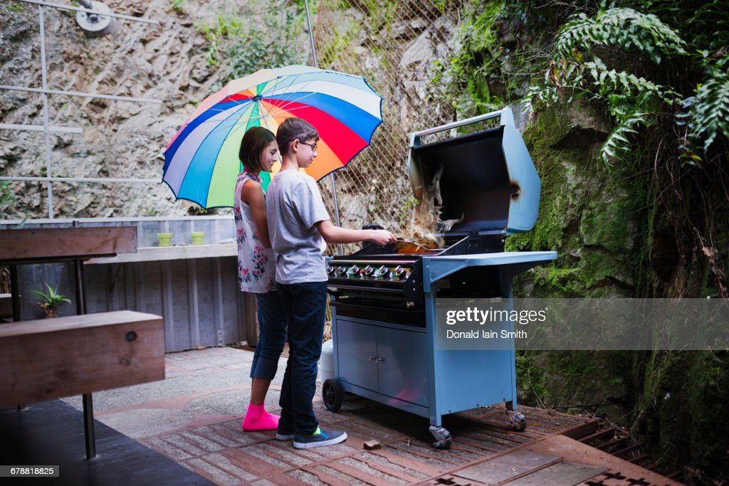 Mixed Race Brother And Sister Cooking On Patio Grille Under ...
