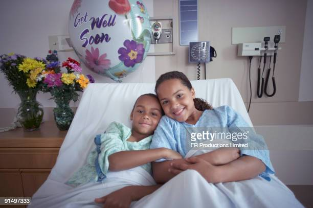 mixed race brother and sister in hospital bed - patients brothers stock pictures, royalty-free photos & images