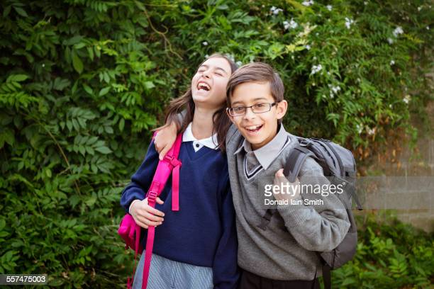 Mixed race brother and sister laughing in school uniforms