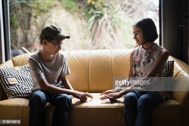 Mixed Race brother and sister playing finger game on sofa near window