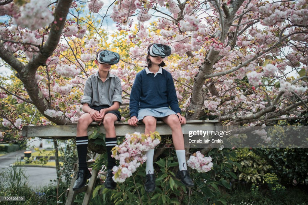 Mixed Race brother and sister sitting in tree wearing virtual reality goggles : Photo