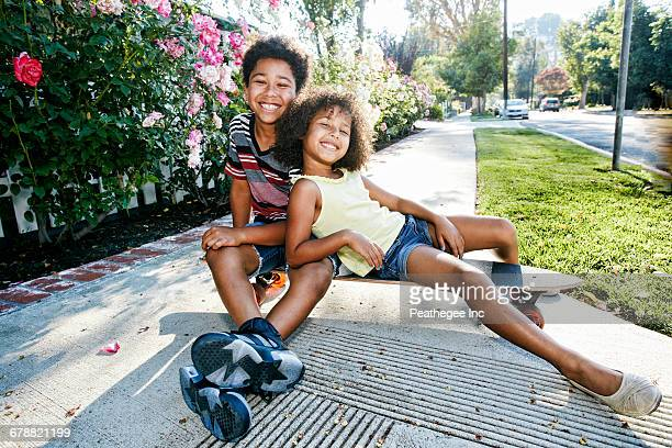 Mixed Race brother and sister sitting on skateboard on sidewalk
