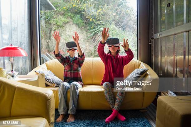 Mixed Race brother and sister using virtual reality goggles on sofa