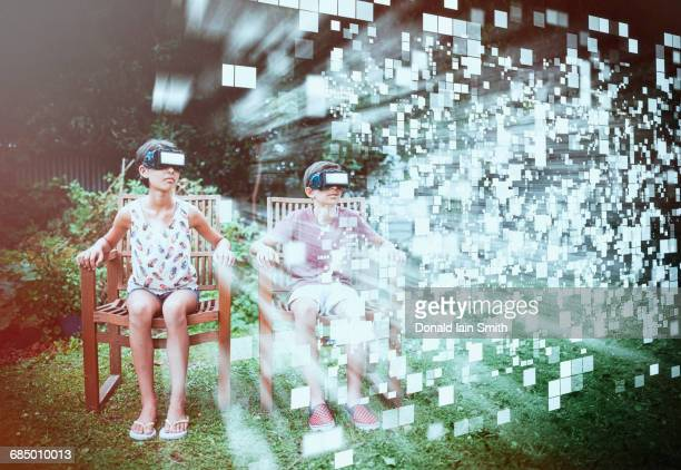 Mixed Race brother and sister viewing hovering pixels with vr goggles